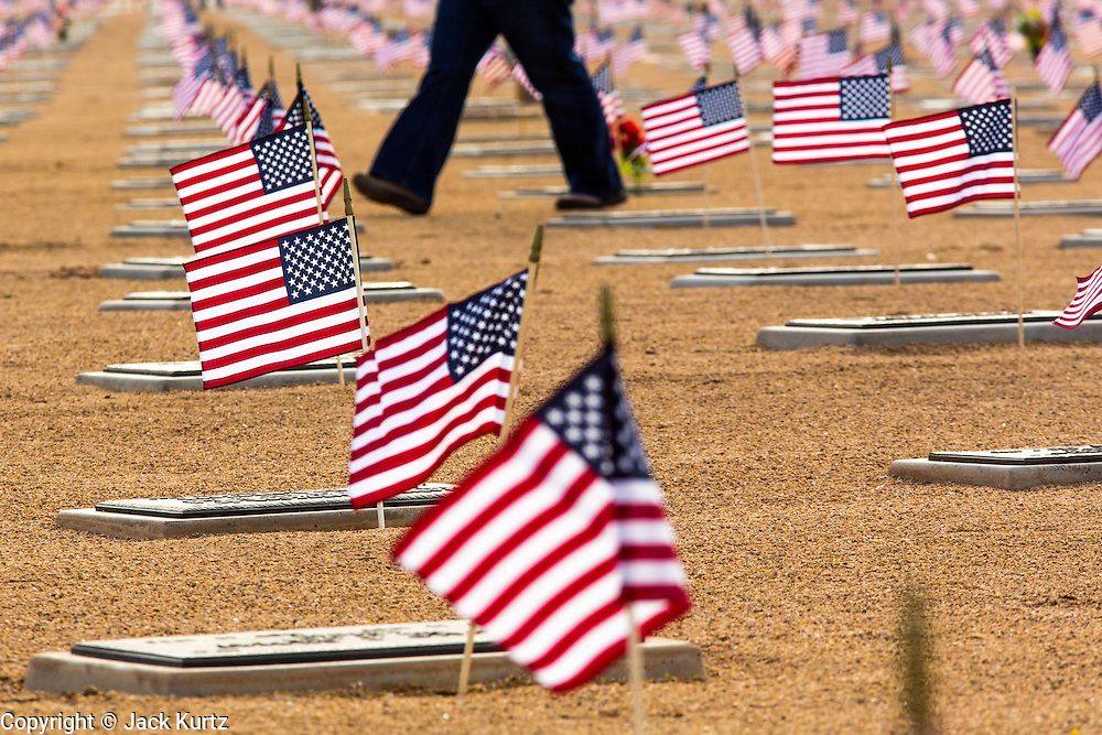 26 MAY 2012 - PHOENIX, AZ: A man walks through the National Memorial Cemetery in Phoenix, AZ, Saturday. Hundreds of Boy and Girl Scouts along with the Young Marines, a Scout like organization, place American flags on veterans' graves in the National Memorial Cemetery in Phoenix every year on the Saturday before Memorial Day.   PHOTO BY JACK KURTZ