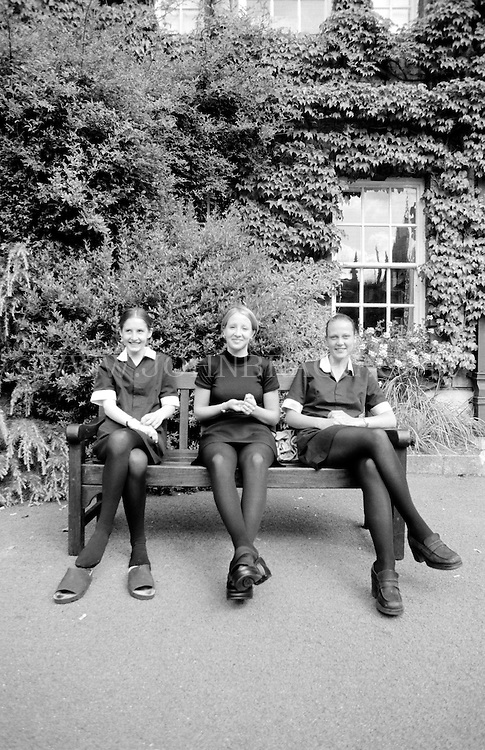 Black and white photo of three women on a bench in Oxford, England.