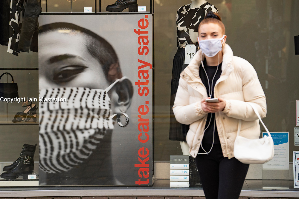 Glasgow, Scotland, UK. 26 October 2020. View of Glasgow city centre on weekday during circuit breaker lockdown with bars and restaurants closed. Pictured; Woman wearing facemask outside shop window display in Primark store. Iain Masterton/Alamy Live News