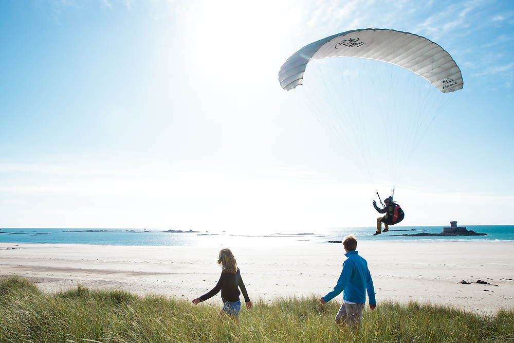 Couple walking through the sand dunes at St Ouen's Bay, Jersey, watching a paraglider coming down to land on the beach in front of the landmark, La Rocco Tower, on a sunny day in summer.