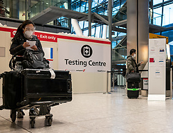 © Licensed to London News Pictures. 17/01/2021. London, UK. A passenger queue passes a testing centre at London Heathrow. Passengers arriving from abroad on Monday morning will have to show that they have had a negative Covid-19 test. Today, Foreign Secretary Dominic Rabb, said that lockdown could be lifted in March but with tier systems in place as health chiefs reveal that a 24/7 vaccination pilot will begin next week as total Covid-19 deaths reach over 88,000 this weekend. Photo credit: Alex Lentati/LNP