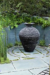 Slate urn sculpture as focal point. Slate paving engraved with words. The Cumbrian Fellside Garden. Design: Kim Wilde and Richard Lucas - Chelsea 2005