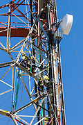 Riggers working on television broadcast tower installing radio system on Mount Stuart, Townsville, Queensland, Australia <br />