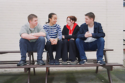 Group of teenagers sitting outside on bench talking,