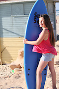 Young girl of 12 on the beach with her surfboard