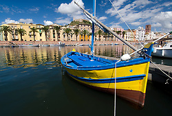Small boat on river in centre of Bosa town on Sardinia in Italy