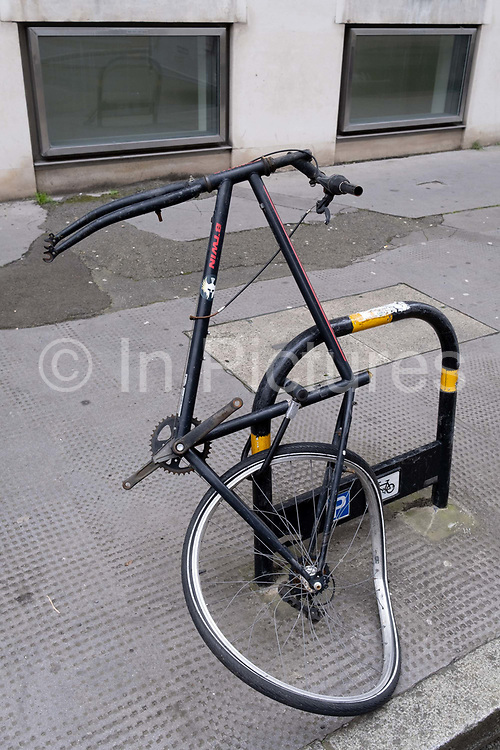 The frame and just a few parts remain of a vandalised bike left locked to a post that once belonged to a cycling City commuter in the financial district, on 11th January 2021, in the City of London, England.