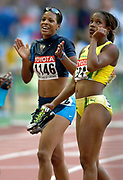 Gahr High graduate Miesha McKelvy (left) celebrates third-place finish in the 100-meter hurdles in the IAAF World Championships in Athletics at Stade de France. Photo by Kirby Lee.