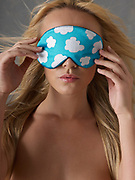 Close up of woman's face holding a sleeping mask with cloud pattern over eyes