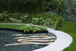 Curved white stone path around pool with planting of Stipa tenuissima