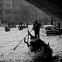 Gondolier passing under bridge Venice