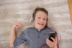 Boy at home listening to music from smartphone