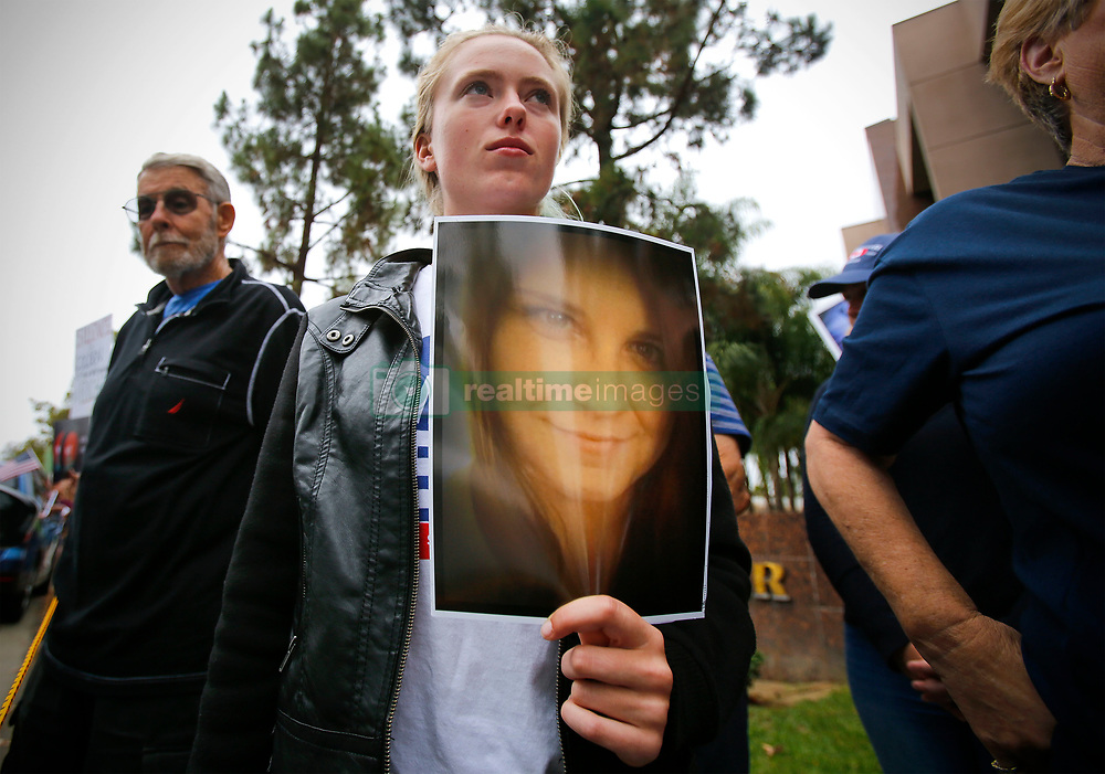 August 15, 2017 - Vista, California, USA - Beryl Lewis of Carlsbad holds a photo of Heather Heyer, during  moment of silence at the weekly rally in front of Congressman Darrell Issa's Vista office, protesting the congressman, and President Trump. Heyer, protesting at white supremacy rally in Charlottesville, Virginia,  was killed last Saturday, after a car crashed into demonstrators. (Credit Image: © Howard Lipin/San Diego Union-Tribune via ZUMA Wire)