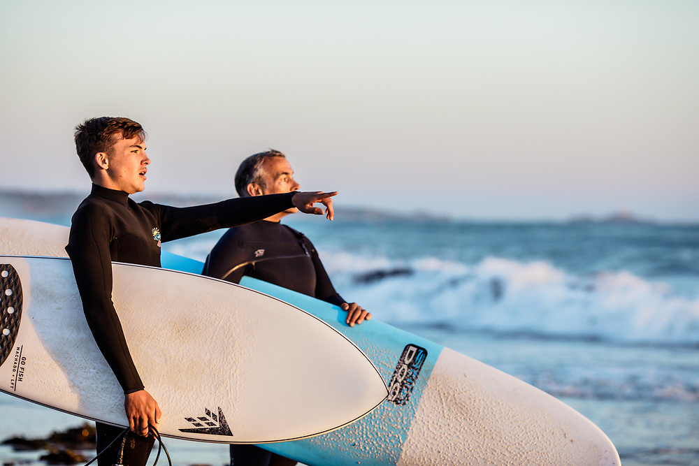 Father and son holding their surfboards watching the waves and surf at St Ouen's Bay, Jersey at sunset