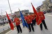 People waving the Albanian national flag are gathered outside the government building in the capital Pristina, to celebrate the tenth anniversary of the Kosovo Liberation Army and its known Legendary Commander, Adem Jashari. A parade was also organised by the Kosovo Protection Corps (KPC) at the presence of Kosovo Prime Minister Hashim Thaçi, President Fatmir Sejdiu, Assembly speaker Jakup Krasniqi and other political and cultural representatives. (Photo by Vudi Xhymshiti)