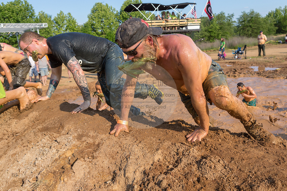 Men climb out of a muddy watering hole during a race at the 2015 National Red Neck Championships May 2, 2015 in Augusta, Georgia. Hundreds of people joined in a day of country sport and activities.