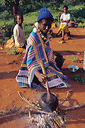 The Northern Province of South Africa, formerly the Northern Transvaal and now called the Mpumalanga, is home to the Vendan people. Here, Muditami Munzhedzi, in traditional Venda clothing, prepares the Vendan's daily staple of cornmeal porridge as well as mopane worms. Tshamulavhu, Mpumalanga, South Africa. (Man Eating Bugs page 134)