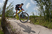 A mountain biker clears a jump at speed