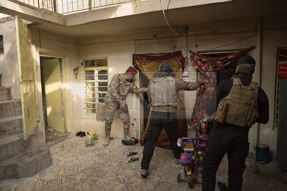 Licensed to London News Pictures. 13/02/2017. Mosul, Iraq. Iraqi National Security Service officers search a house for a suspected ISIS fighter during a raid in the city.<br /> <br /> The Jihaz Al-Amin Al-Watani, roughly translated as the National Security Service or NSS, are a secretive Iraqi agency that works under the responsibility of the Ministry of Interior. Since the liberation of eastern Mosul in January 2017 the NSS have been actively hunting down ISIS members who stayed behind to continue terrorism as part of sleeper cells and residents who worked with the group during its two year occupation. Recruiting from across the country agency is responsible for internal security inside Iraq and has a broad remit to investigate and arrest everything from terrorists and foreign spies to financial criminals and drug traffickers. Photo credit: Matt Cetti-Roberts/LNP