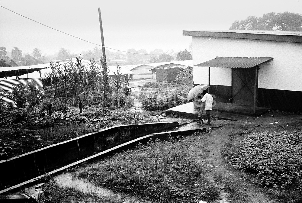 A father and son, both amputees, walk to their tent in the rain. Murraytown amputee camp, Freetown, Sierra Leone 1999