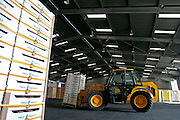 Large tractor carrying pienapple crates in warehouse.