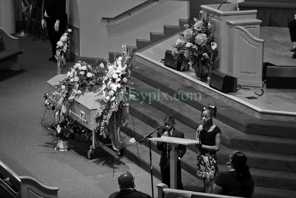 03 June 2014. New Orleans, Lousiana. <br /> Siblings sing a tribute at the funeral of teenage shooting victim Dwayne Matthew Joseph at the Franklin Avenue Baptist Church. 17 year old Joseph was shot and killed following an altercation in the street May 26th. Raised by his great grandmother Catherine Robinson, family and friends confirmed Dwayne was a good kid who went to church, looked after his younger siblings and had never been in trouble with the law. Dwayne's older brother Damien preceded him in death. He too was shot dead in February 2011 aged just 19 years.<br /> Photo; Charlie Varley/varleypix.com