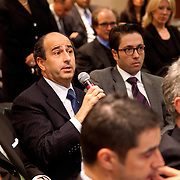 Man speaking into hand held mic in audience of a business presentation