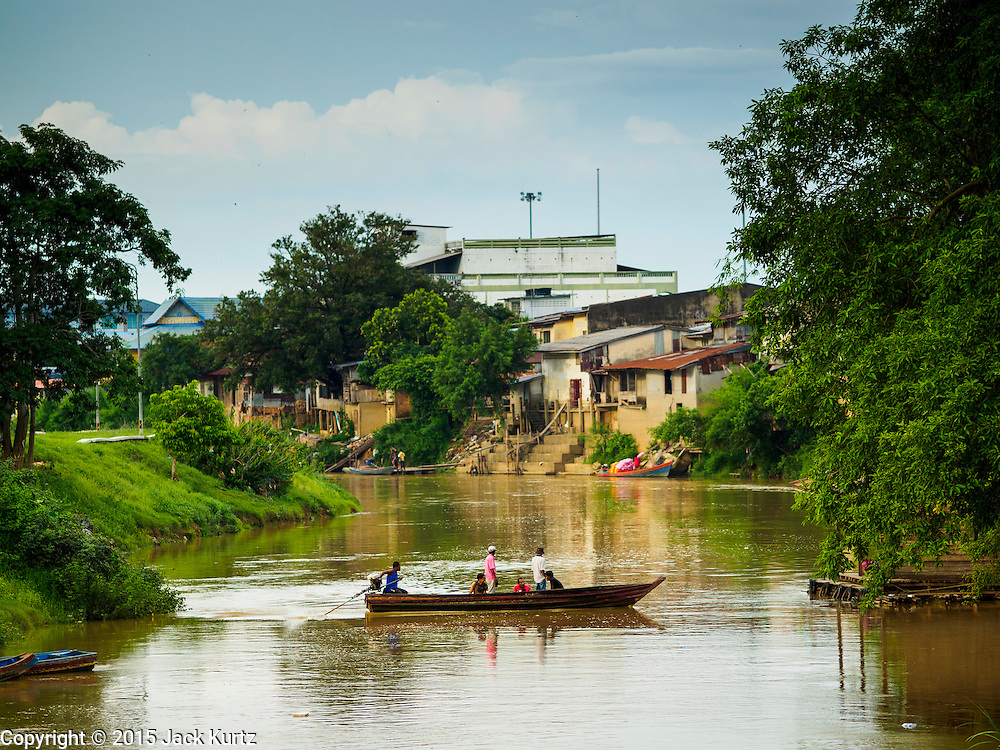 16 JUNE 2015 - SUNGAI KOLOK, THAILAND:  A small boat crosses from Thailand to Malaysia in Sungai Kolok, Thailand. The border between Thailand and Malaysia in Sungai Kolok, Narathiwat, Thailand. Thai and Malaysians cross the border freely for shopping and family visits. The border here is the Kolok River (Sungai is the Malay word for river).        PHOTO BY JACK KURTZ