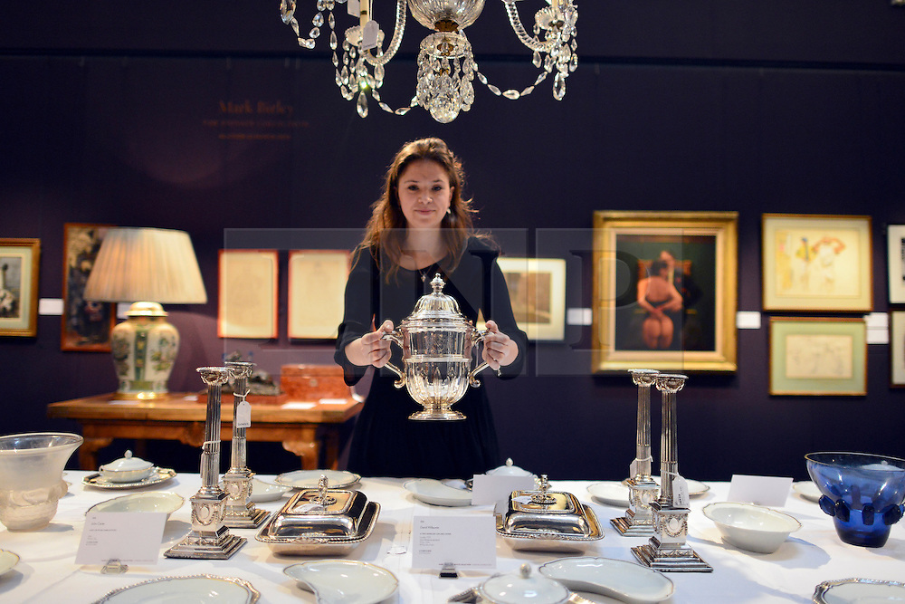 © Licensed to London News Pictures. 18/03/2013. London, UK An assistant holds a silver Two Handled Cup and Cover with an estimated value 2,000 -5,000GBP. of Press call for The Collection of Mark Birley at Sotheby's auction house today 18th March 2013. Mark Birley was the owners of members only clubs Annabel's, Mark's Club, George's Bar, Harry's Bar and The Bath and Racquets Club in London. Photo credit : Stephen Simpson/LNP