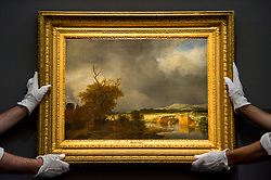"""© Licensed to London News Pictures. 07/12/2020. LONDON, UK. Technicians present """"Landscape with a cottage and stone bridge under a cloudy sky"""", by Jacob Isaacksz. van Ruisdael (Est. £800k-1.2m). Preview of Sotheby's upcoming Christmas Sale Series of Old Masters and Treasures - paintings and objects spanning 800 Years.  The sales will be at Sotheby's New Bond Street gallery.  Photo credit: Stephen Chung/LNP"""