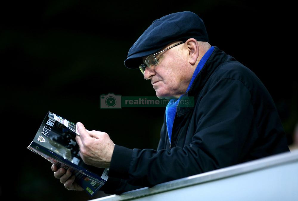 An AFC Wimbledon fan reads through a match programme before the game begins