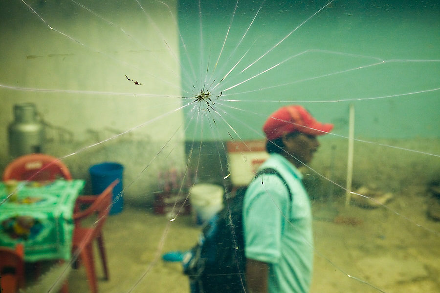 A man walks past the tables and chairs of a street-side eatery in San Cristobal de las Casas, Chiapas state, Mexico on June 26, 2008. The scene was photographed through a cracked public bus window.
