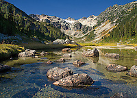 A clear and pure lake is dotted with glacial rocks in Brandywine Meadows, near Whistler, BC Canada