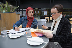 Two students; working together at an outdoor café,
