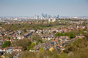 Londons skyline from Dawson's Heights in Dulwich, London, England, United Kingdom. Residential homes on streets of terraced housing and in the distance skyscrapers rise in the financia district of Canary Wharf.