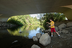 United States, Washington, Redmond, boy  under bridge on Sammamish River Trail  MR