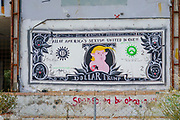 Dollar Trump Graffiti. A dollar bill with a colorful caricature of Donald Trump as the portrait of the president. With the words: All of America's Sexism United in One