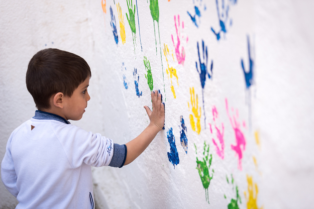 17 February 2020, Zarqa, Jordan: A boy paints her handmark on the wall of the Lutheran World Federation community centre in Zarqa. Through a variety of activities, the Lutheran World Federation community centre in Zarqa serves to offer psychosocial support and strengthen social cohesion between Syrian, Iraqi and other refugees in Jordan and their host communities.