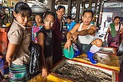 13 JUNE 2013 - YANGON, MYANMAR:   Workers sort shrimp and prawns in the Annawa Fish Market. The Annawa Fish Market in Yangon is one of the largest fish markets in Myanmar. It serves as both a wholesale and retail market and serves both exporters and domestic customers. With thousands of miles of riverine waterways and ocean coastline Myanmar has a large seafood and fishing industry.   PHOTO BY JACK KURTZ