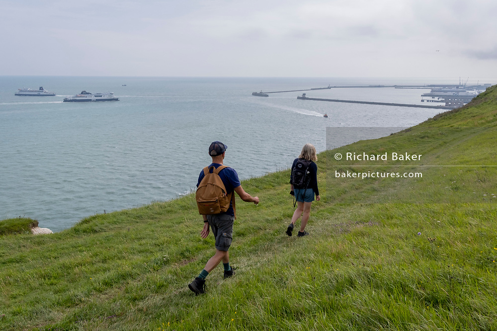 Overlooking cross-Channel ferries and Dover Dock's harbour wall in the distance, walkers stride along the clifftop footpath, near the edge of England's iconic White Cliffs, under threat from chalk and soil erosion, on 27th July, at Langdon Bay, Dover, in Kent, England.