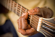 An elderly african-american blues musician plays his acoustic guitar