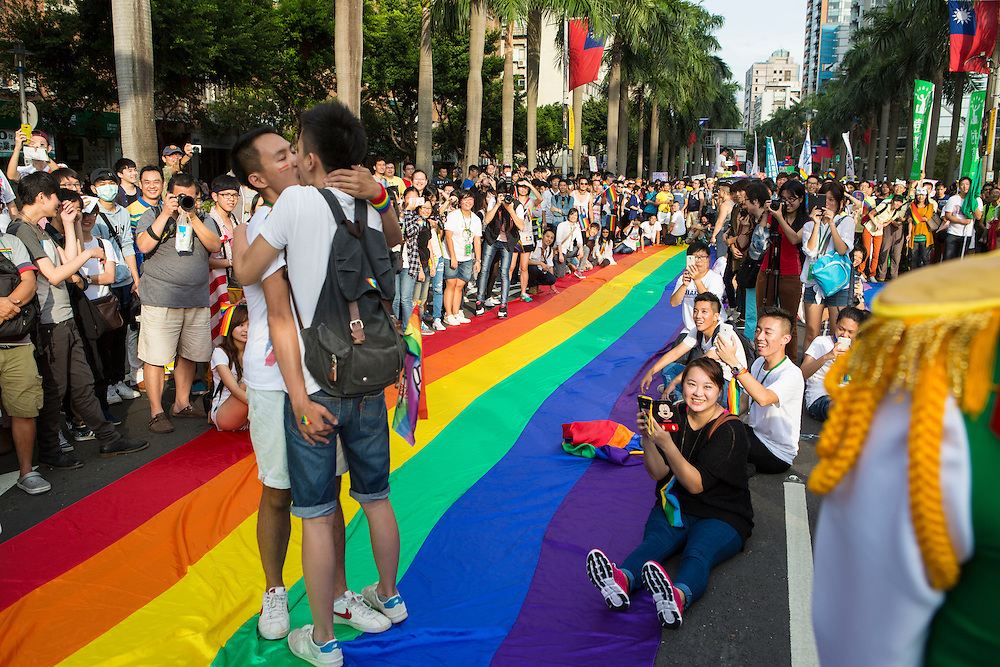 """Two gay men kiss standing on the rainbow banner, cheered on by an enthusiastic crowd at the pride parade. The annual march through Taipei's city streets is the largest in Asia, with well over 50 000 people taking part. The 2014 event had the theme """"Walk in Queer's Shoes"""", to encourage the wider community to lend their support for equal marriage rights."""