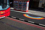 On the day that UK Prime Minster, Boris Johnson announced in parliament of a major easing of Coronavirus pandemic restrictions on July 4th next week - including the re-opening of pubs, restaurants, hotels and hairdressers in England - a London bus is seen stopped in front of double Red Route no parking lines and a rainbow, a symbol of support for NHS and key workers during the pandemic, on 24th June 2020, in London, England. The three month two metre social distance will be also reduced to one metre plus but in the last 24hrs, a further 154 UK covid deaths are reported, bringing the total to 43,081 victims during the Coronavirus pandemic.
