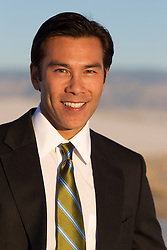 Asian American man in a suit and tie outdoors