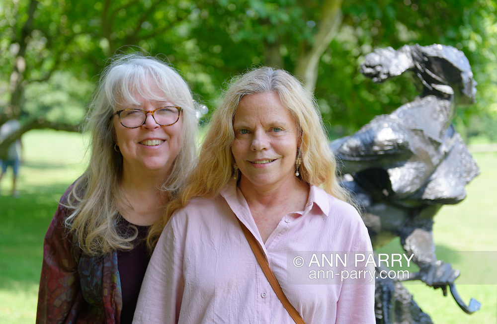 """Roslyn, New York, U.S. July 7, 2019. Visitors Pamela Waldroup and Margaret pose next to bronze sculpture """"Girl on a Bicycle """"(1964) by Bruno Lucchesi, on the grounds of the Nassau County Museum of Art, Long Island."""