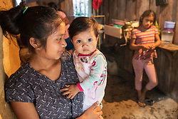 """Lourdes López Vásquez, 16, with her baby Saida, 9 months old. <br /> <br /> """"The family was evacuated at midnight, that was during hurricane Eta. We heard thundering noises coming from underground, from inside the mountain"""" said Lourdes, """"We were all evacuated, it was dark, we all felt sad"""". Lourdes' family is one of 60 families affected by the landslide in the village of El Zapote, San Luis Planes, Santa Bárbara. That night six houses were destroyed by a landslide there and another 55 were made unsafe by subsidence, and have now been declared uninhabitable. The region of Santa Bárbara, with steep mountain slopes that are ideal for coffee growing, is particularly prone to landslides. Fairtrade-certified cooperative Montaña Verde is based in San Luis Planes and coop members are all affected by climate change, hurricanes and landslides. Serious problems with access to farms, loss of land, loss of topsoil, washed-out nutrients, the early fall of unripe cherries, leaf drop, root rot, and a proliferation of fungal diseases all affect the producers, as well as the loss of their corn and bean crops that they rely on as their staple food."""