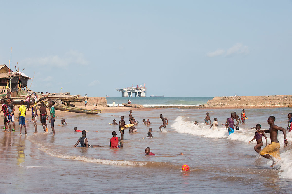 People enjoy the beach of New Takoradi in front of the large oil tanks and commercial harbour, Ghana 2011