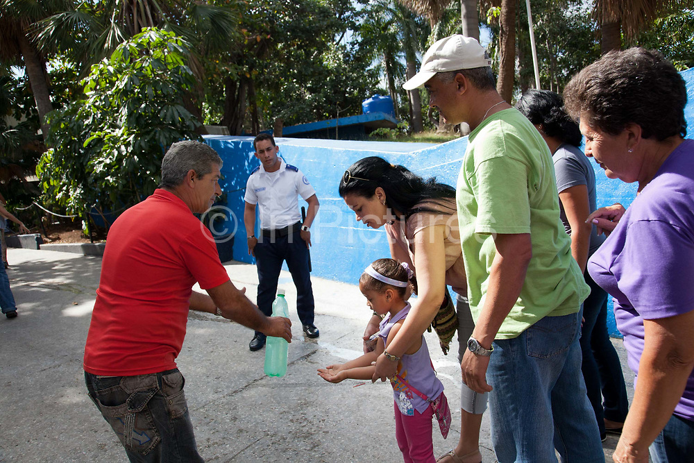 Cuban family having their hands washed at the entrance to an ice cream parlour, this was protection againist a virus that was spreading around the country at the time.