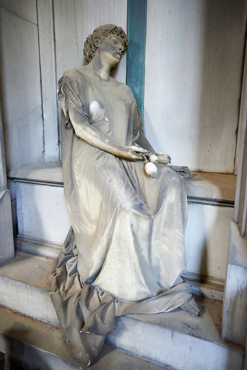 Picture and image of the Neo Gothic Erba stone tomb sculpture of a female figure, with her eyes closed and some poppy seeds in her hands, which are a pagan symbol with a funeral meaning because of their narcotic properties. The garment, stretching along her arm, leaves one shoulder undressed, thus giving the sleeper a touch of sensuality that did not fail to arouse some controversy among the contemporaries. By Sculptor Sculptor S. Saccomanno 1883.  Section A, no 50, The monumental tombs of the Staglieno Monumental Cemetery, Genoa, Italy .<br /> <br /> Visit our ITALY PHOTO COLLECTION for more   photos of Italy to download or buy as prints https://funkystock.photoshelter.com/gallery-collection/2b-Pictures-Images-of-Italy-Photos-of-Italian-Historic-Landmark-Sites/C0000qxA2zGFjd_k<br /> If you prefer to buy from our ALAMY PHOTO LIBRARY  Collection visit : https://www.alamy.com/portfolio/paul-williams-funkystock/camposanto-di-staglieno-cemetery-genoa.html