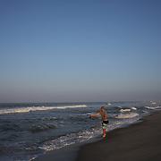 An early morning beach scene at Cisco Beach, Nantucket, as a fisherman casts his rod. Nantucket Island, Massachusetts, USA. Photo Tim Clayton